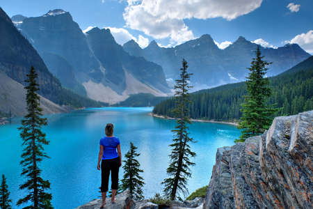 Woman on cliff looking at Moraine Lake.  Rocky Mountain. Banff National Park, Alberta, Canada.