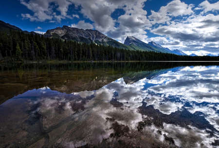 canadian rockies: Clouds reflections in lake. Honeymoon lake in Canadian Rockies. Jasper National Park. Alberta. Canada. Stock Photo