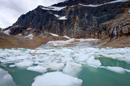 thawing: Alpine lake with ice. Angel Glacier at Mount Edith Cavell. Jasper National Park. Canadian Rockies. Alberta. Canada. Stock Photo