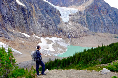 Man hiker on rocks viewing alpine lake and Angel Glacier at Mount Edith Cavell. Canada.