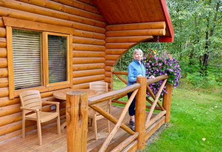 Roche Miette Hot Spring, Alberta/Canada - September 2, 2016: Vacation cabins Pocahontas. Woman stands on porch of a new wooden cabin.