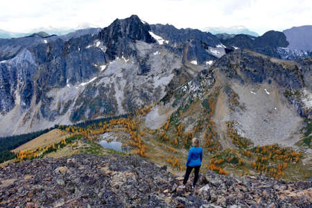 Woman on cliff. Frosty Mountain. Manning Provincial Park. Hope. British Columbia. Canada.