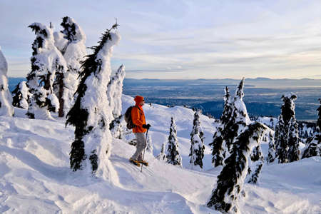 Man walking in mounatains in winter. Mount Seymour Provincial Park. Vancouver. British Columbia. Canada.