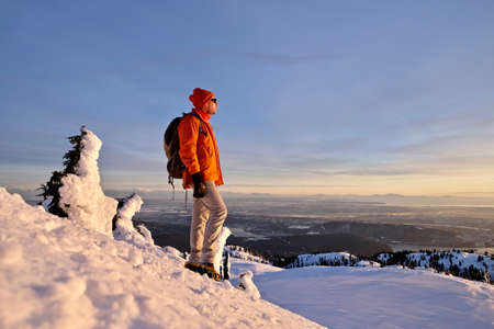 Man watching sunset from mountain top in winter. Mount Seymour Provincial Park. Vancouver. British Columbia. Canada.