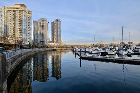 Seawall, bulidings, boats in marina and their reflections in calm water. Yaletown. Cambie Bridge. False Creek.  Vancouver downtown. British Columbia. Canada.