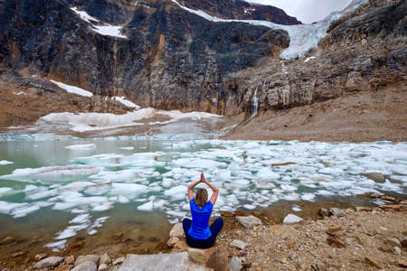 Woman doing yoga stretching by a moraine lake in Rocky Mountains. Angel Glacier at Mount Edith Cavell. Jasper National Park. Canadian Rockies. Alberta. Canada.
