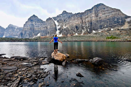 Blond woman by alpine lake enjoying the mountain view on a rainy day. Eiffel lake hike from Moraine lake lodge. Banff National Park. Canadian Rockies. British Columbia. Canada.
