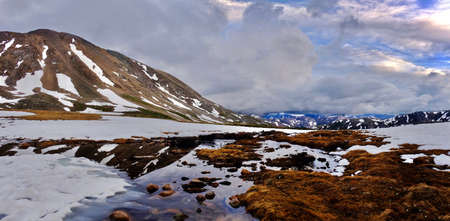 tarn: Storm clouds over mountains and reflection in water. Snow thawing on Independence Pass. Aspen. Colorado. United States.