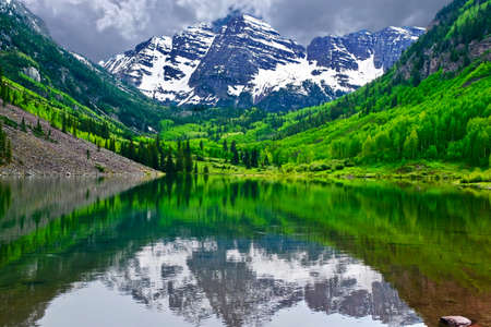 Mountain peak reflection in calm lake. Maroon Bells near Aspen, Snowmass,  Colorado State, USA. Фото со стока