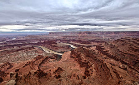 switchback: Winding road in endless canyons, river bend and storm sky.  Dead Horse Point. Canyonlands Natioanal Park. Moab. Utah. United States. Stock Photo