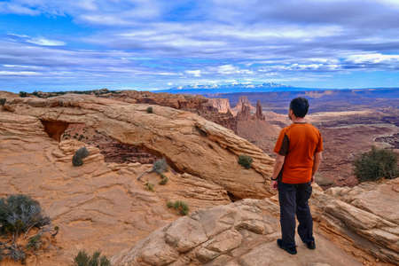Man hipster on cliff looking at canyon views. Mesa Arch in Canyonlands National Park. La Sal Mountains. Moab. Cedar City. Utah. United States.