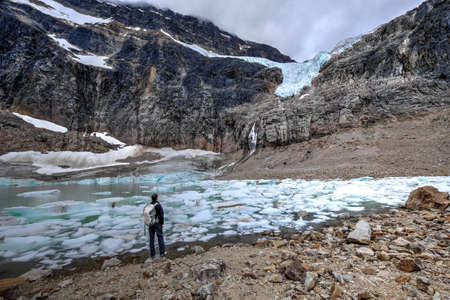 Man backpacker by a moraine lake and glacier. Mount Edith Cavell. Angel Glacier. Canadian Rockies. Jasper National Park. Alberta. Canada. Stock Photo