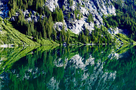 campsite: Calm lake reflection in Cascade Mountains. Upper Snow Lake. The Enchantments. Leavenworth. Seattle. WA. USA