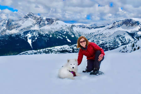 Young smiling woman and dog in mountains. Snowshoeing in Whistler Balckcomb. Vancouver. British Columbia. Canada.