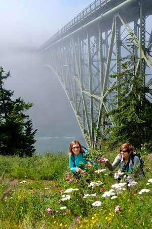Happy women hiking by ocean in foggy morning. Deception Pass Bridge State Park.  Anacortes. Seattle. Puget Sound. Juan de Fuca Strait. Washinton. United States.