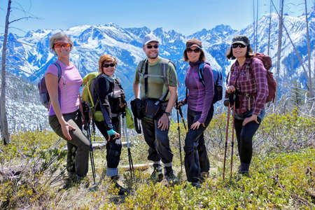 Group of friends hiking in mountains. Smiling happy people full length. Icicle Ridge in Central Cascade Mountains. Leavenworth. Seattle. Washington. United States. Stock Photo