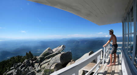 wa: Young man hipster on mountain hut looking at views. Mount Pilchuck. Seattle. Washington. United States. Editorial
