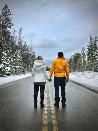 Young couple standing on road holding hands. Newlyweds near Revelstok. British Columbia. Canada. Standard-Bild