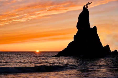 Sunset at Rialto Beach. Sea stack silhouette by sunset sky. Seattle. Stock Photo