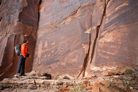 Man looking at rock art of Pueblo Indians. Owl, thunderbird, goat and a man figure petroglyphs on sandstone wall near Moab in Utah. Moab. Utah. United States.