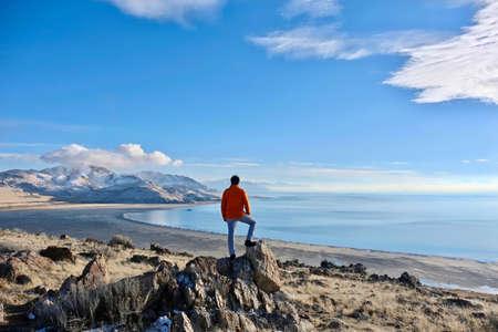 Reisen nach Great Salt Lake und Antelope Island an einem Wintertag. Bemannen Sie Wanderer auf einer Klippe über dem See, der die szenischen Ansichten genießt. Salt Lake City. Antelope Island State Park. Utah. Vereinigte Staaten.