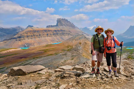 Happy family  travelling in Canadian Rockies. Active man and woman hikers  on trail. Dolomite Mountains in Banff National Park. Rocky Mountains.  Alberta. Canada.