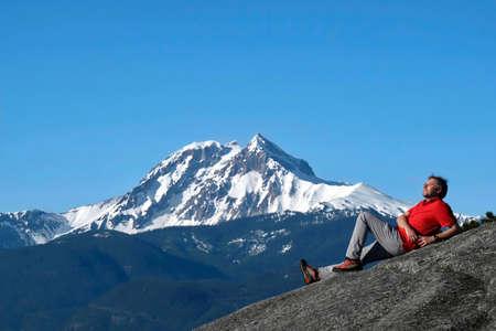 Man on mountain top against snowcapped Diamond Head peak. Stawamus Chief park near Squamish. British Columbia. Canada.