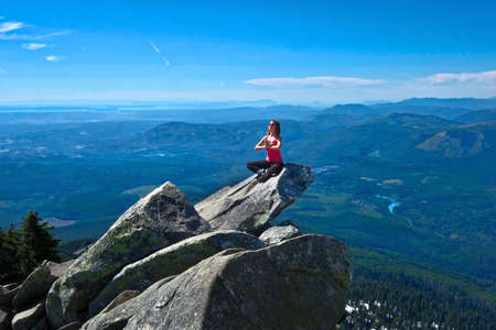 Young woman meditate on rock above beautiful valley. Mount Pilchuck summit in North Cascades Mountains. Skagit Vallley near Seattle. Washington State. United States of America. Stock Photo