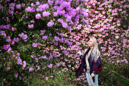Beautiful blond woman in rhododendron garden. Pink and purple rhododendron flowers in full bloom in Queen Elizabeth Garden. Vancouver. British Columbia. Canada.