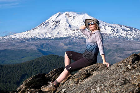 Summer vacation travel in Oregon. Middle age woman relaxing on mountain top by glacier on Mount Adams.  Portland. Oregon. United States of America.