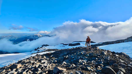 Hiking in Washington State. Man hiker walking up mountains above clouds. Rocky mountain and snow.  Mount Rainier National Park. Seattle. WA. United States of America.