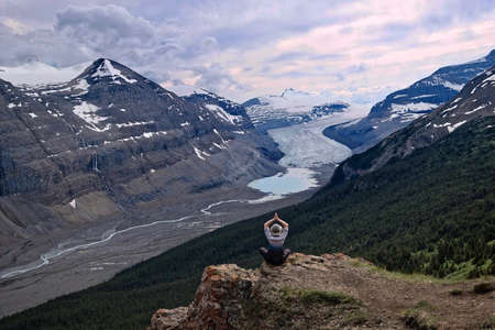 Woman meditating on steep cliff over Columbia Icefield glacier and a moraine lake.  Outdoor yoga in  Banff  Jasper National Park. Canadian Rocky Mountains.  Patterson Ridge trail. Alberta. Canada. Stock Photo
