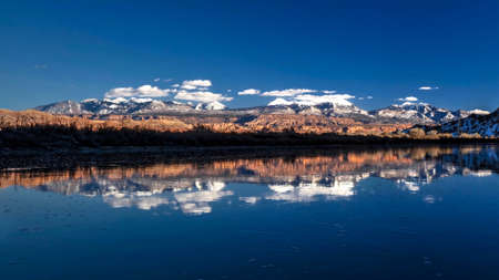 Snow capped La Sal mountains and their reflections in Colorado River in winter. Wilderness near Moab. Utah. The United States of America.