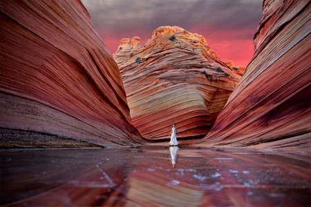 Woman standing on frozen lake in colourful canyon at sunrise.  The Wave. Vermillion Cliffs near Page. Arizona. The United States of America. Imagens