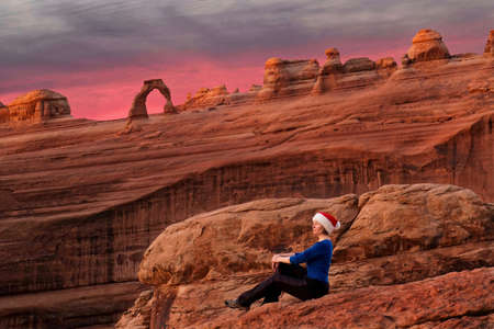 Woman sitting at viewpoint of Delicate Arch at sunrise. Christmas time in Utah. Moab. USA
