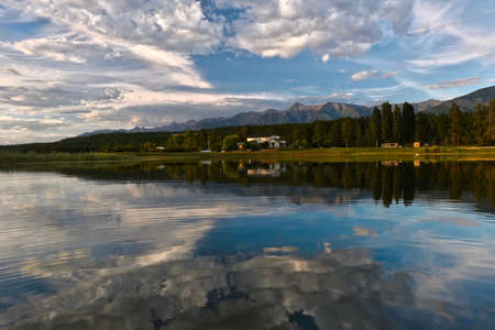 Panoramic view of mountains, trees and a country house in calm lake in the morning. Columbia lake. British Columbia. Canada