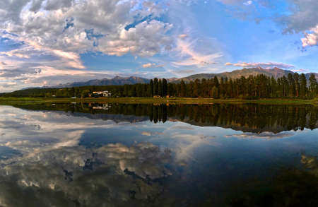 Panoramic view Columbia Lake. Beautiful reflections of mountains, trees and a little house in calm lake at sunrise. Columbia lake. British Columbia. Canada Imagens