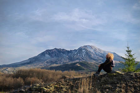 Woman sitting on rock in Mt St Helens National Volcanic Monument.  Hiking in Washington State.  United States of America