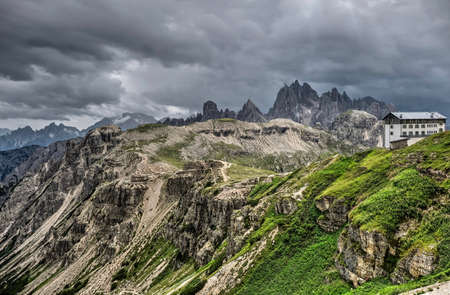 Storm clouds over Dolomites.  Travel Italy. Scenic view from Tre Cime towards a mountain hut. South Tyrol. Italy.