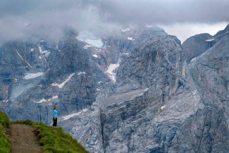 Summer hiking in Dolomites, Italy. Middle age woman standing on trail and enjoying view of Mount Mormalada with glaciers and snow. Canazei.  South Tyrol. Italy. Фото со стока