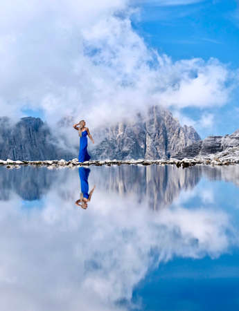 Young pretty woman with long blond hair by alpine lake with mountains reflections. Vacation travel in Italian Alps. Dolomites mountains.  South Tyrol. Canazei. Italy.