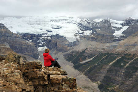 Woman sitting on cliff looking at scenic view of Victoria Glacier. Woman hiking in Canadian Rocky Mountains.  Fairview mountain. Banff National Park. Alberta. Canada.