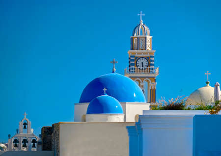 Blue domes under blue sky  in Santorini island. White buildings and blue domes of greek church. Summer in Greece.