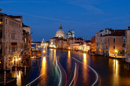 Accademia bridge at sunset. View from Accademia Bridge in Venice. Colorful light treks from boats lights against dark canal water. Venice.  Italy.