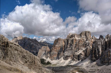 Scenic view in Italian Dolomites mountains. Rocks and peaks under blue sky with white puffy clouds. Falzarego Pass.  Cortina D'Amprezzo. South Tyrol. Italy. Фото со стока