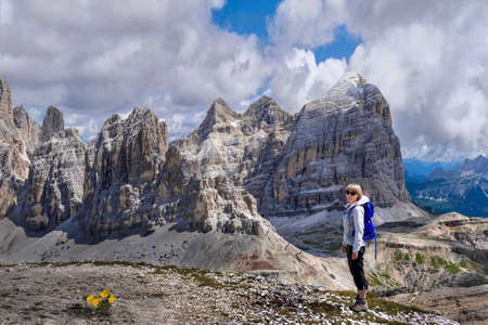 Middle age blond woman in sporty clothes with backpack standing on cliff with yellow poppy flowers enjoying the view of mountains and valleys in Dolomites. Summer travel and hiking in Italian Alps. Cortina DAmprezzo.  South Tyrol. Italy. Stock Photo