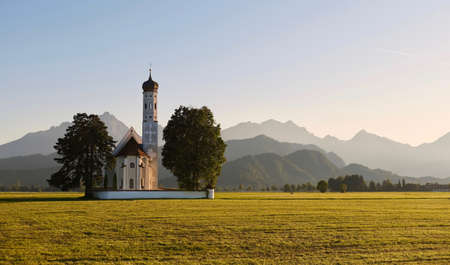 Picturesque landscape in Bavaria. Little old church in green fields with mountain ridge at the background in morning soft light. Bavaria. Germany.