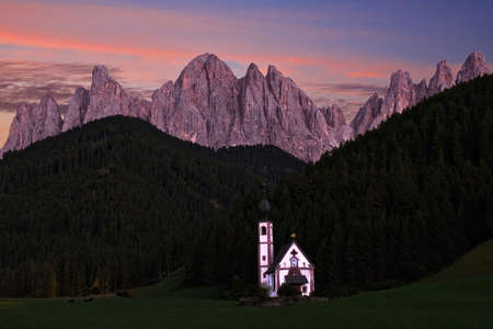 Little pretty old church in green fiels by scenic mountain ridge in Lolomites. San Giovanni Church in Funes Valley. Puez-Geisler Nature Park in South Tyrol. Italy.