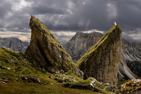 Woman stading on top of sharp rock looking at sunbeams through strom clouds. Mountains and rocks in Dolomites.  Seceda ridge hike in Puez Odle Nature Park . Val Gardena. Italy.
