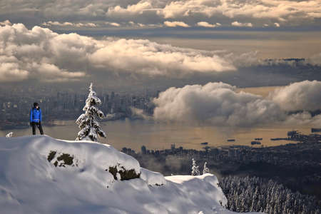 Woman hiker snowshoer standing on a rock above the clouds, ocean and buildings of a big city on a snowy winter day. Scenic view of Vancouver downtown from Seymour Mountain. Winter in British Columbia.